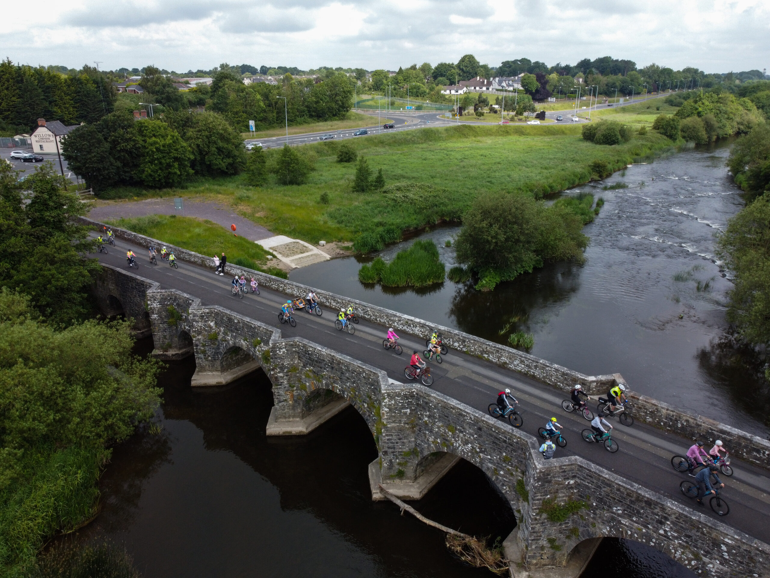 Group of people cycling across the river Boyne at old kilcarn bridge